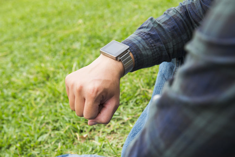 Business Adult Businessman Casual Clothing Close-up Day Field Grass Hand Human Body Part Human Hand Jeans Leisure Activity Midsection Nature One Person Outdoors Plant Selective Focus Time Watch Wrist Wristwatch