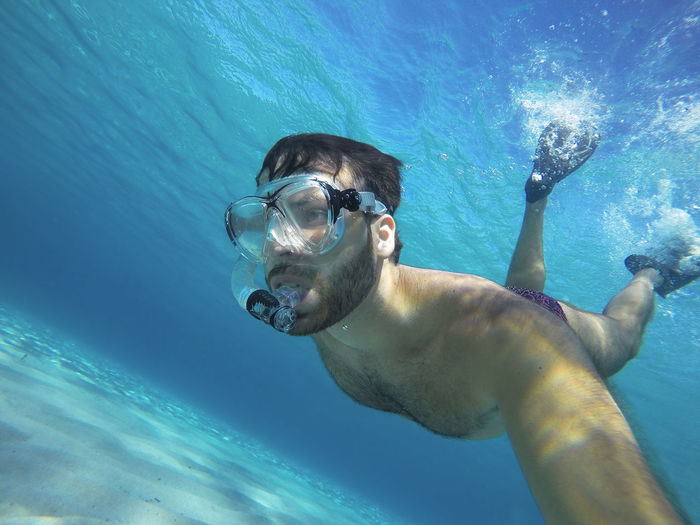 Portrait of young man swimming in sea