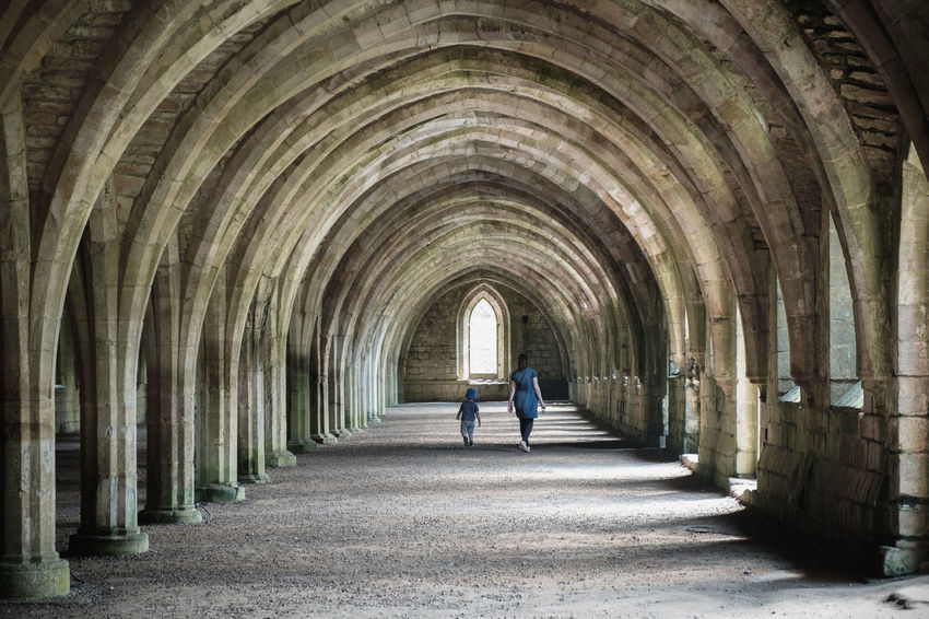 Adult Arcade Arch Architectural Column Architecture Building Built Structure Colonnade Day Diminishing Perspective Direction Full Length In A Row Leaving Light At The End Of The Tunnel One Person Outdoors Real People Rear View Standing The Way Forward Tunnel Walking
