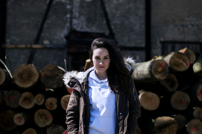 Portrait of smiling young woman standing logs