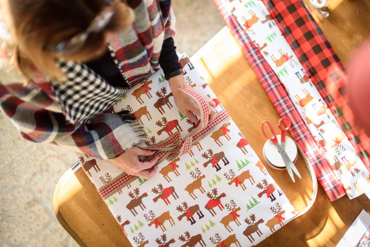 High angle view of woman wrapping gift at home