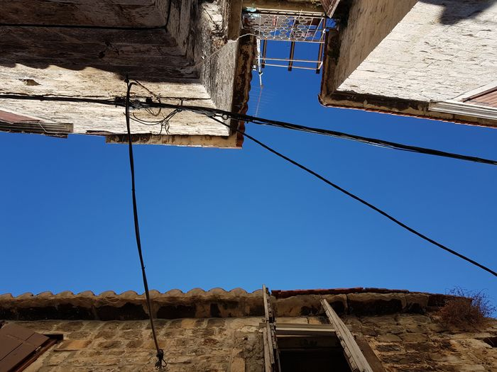 Looking At The Sky Old Town Architecture Blue Building Exterior Built Structure Clear Sky Connecting Houses Connecting People Day Electricity Wires Looking Up Low Angle View Nature No People Old Houses Outdoors Sky