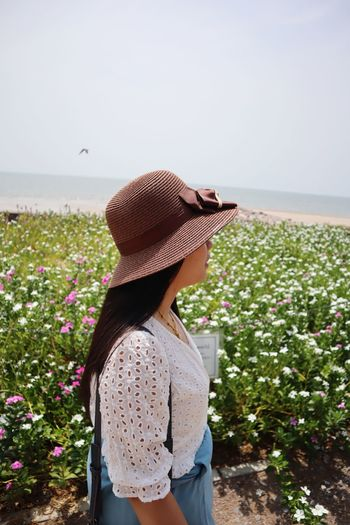 Side view of woman wearing hat standing by plants against clear sky