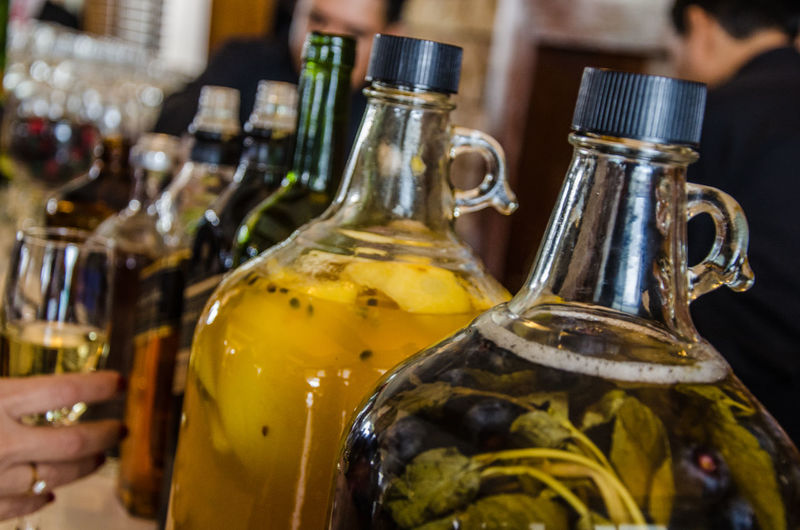 Two large glass bottles of pisco with macerated fruit with the background of a bar Desk Pub Wood Alcohol Backdrop Background Bar Bokeh Counter Decoration Design Drink Interior Layout Lounge Plank Presentation Product Restaurant Shelf Store Surface Table Template Wooden