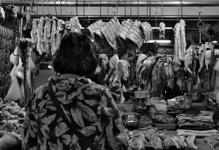 Rear view of woman buying meat at butchers shop