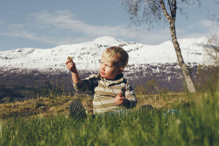 Cute boy sitting on grassy land against snowcapped mountain
