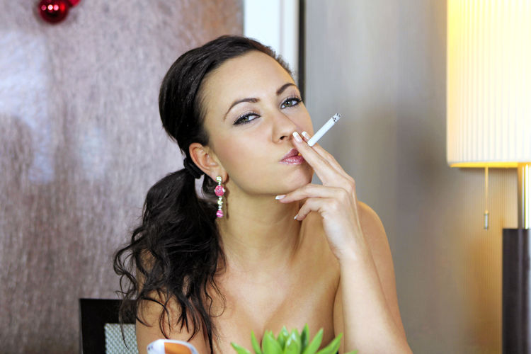 Portrait Of Young Woman Smoking At Home