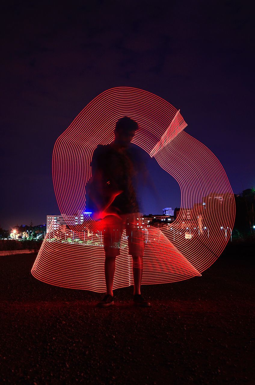 REAR VIEW OF MAN STANDING BY ILLUMINATED FERRIS WHEEL AGAINST SKY