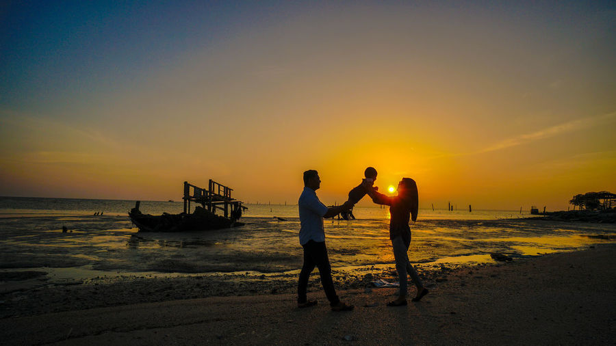 Parents holding baby while standing at beach against sky during sunset