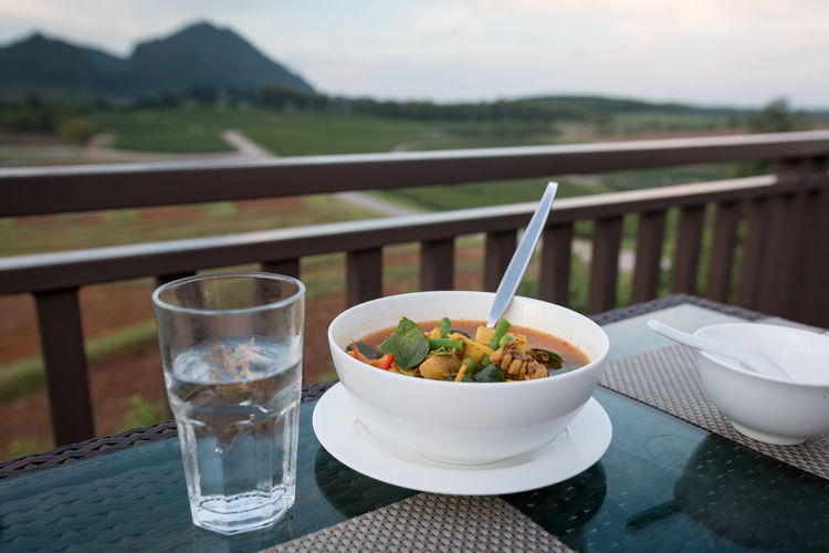 Food in bowl by glass of water on table against landscape
