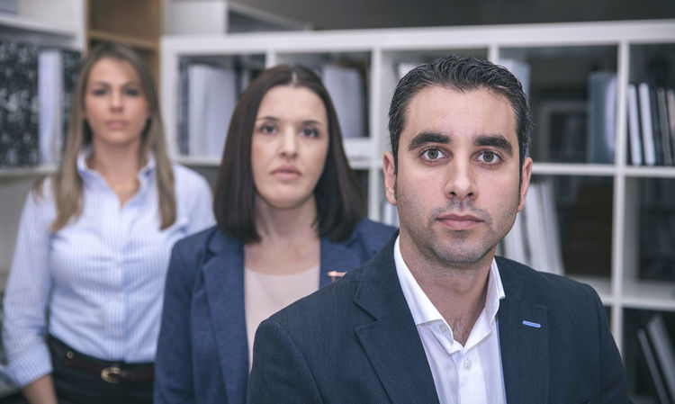 Close up of businessman looking at camera with two female colleagues in the background Business Company Horizontal Man Office Teamwork Woman Working Workplace Business Finance And Industry Businessman Businesswoman Caucasian Chairman Chief Female Headquarters Male People Portrait Professional Seriousface Sucess Team Three People