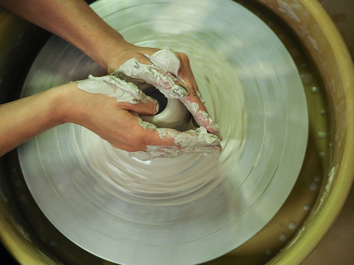 Cropped hand of person working with pottery