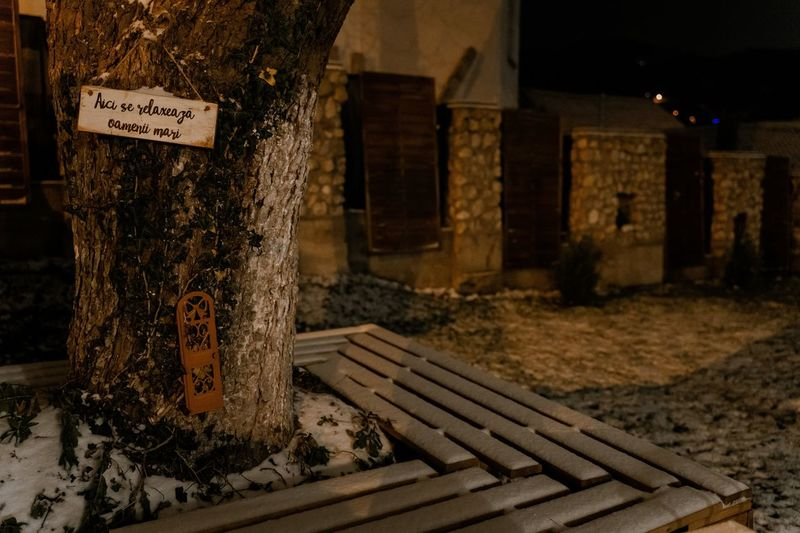 Text on wooden bench against building at night