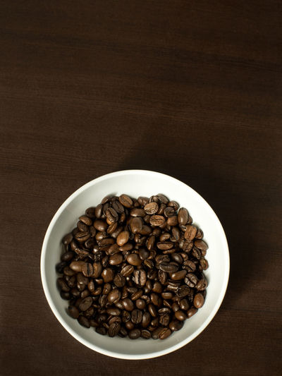 Coffee beans in a white bowl on dark background- coffee minimalism Caffeine Coffee Coffee Time EyeEmNewHere EyeEmReady Food And Drink Backgound Bowl Brown Caffeine Addict Coffee Bean Coffee Beans Dark Background Directly Above Food Porn Freshness Group Of Objects High Angle View Minimal Minimalism No People On White Roasted Coffee Bean Studio Shoot Studio Shot