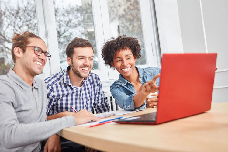 Smiling business persons looking at laptop while sitting at office