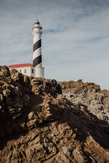 Low angle view of lighthouse on cliff against sky
