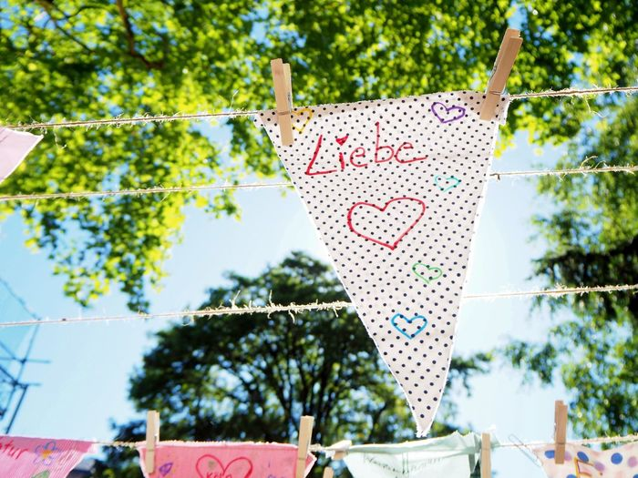 Low angle view of napkin with text hanging on clothesline