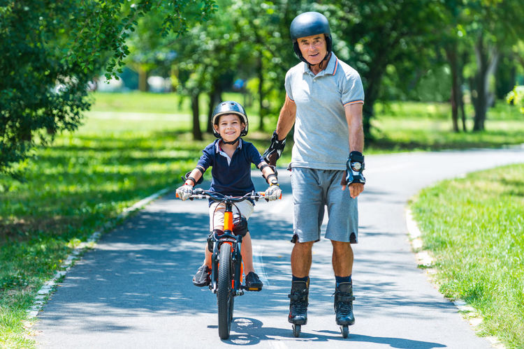 Grandfather And Grandson Biking And Roller Skating Lifestyle Cycle Cyclist Fun Grandfather Grandson Happy Young Bicycle Bike Boy Child Childhood Healthy Helmet Kid Leisure Activity Old Outside Park person Play Ride Senior Summer