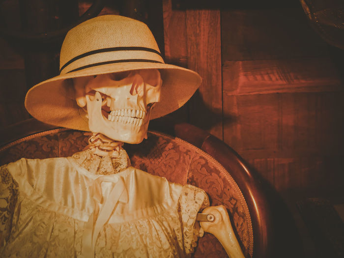 Close-up of human skeleton with hat on chair at home
