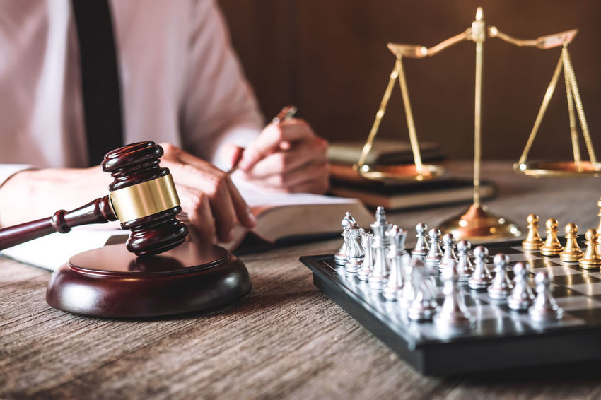 Lawyer Balance Barrister Board Game Chess Close-up Counselor Fairness Game Gavel Hand Holding Human Body Part Human Hand Indoors  Judgement Legal Legislation Leisure Activity Leisure Games One Person Playing Selective Focus Verdict Wood - Material