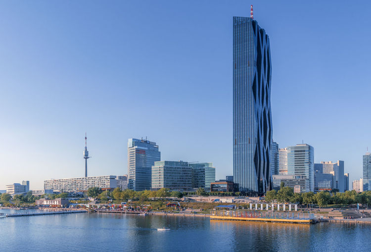 Modern Buildings By River Against Clear Sky