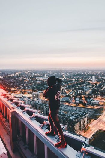 Woman standing on cityscape against sky during sunset