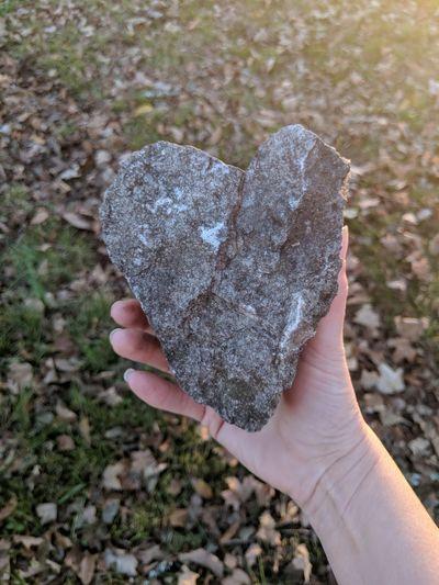 Close-up of hand holding heart shape stone