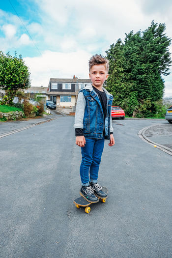 Boy on Street playing Cute Kids Fashion Skateboarding Boy Boys Casual Clothing Child Childhood Day Denim Full Length Kid Lifestyles Neighborhood One Person Outdoors Playing Real People Skateboard Sport Street Trendy Kids Young Boy