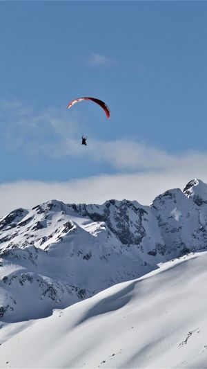 Person paragliding over snowcapped mountain against sky