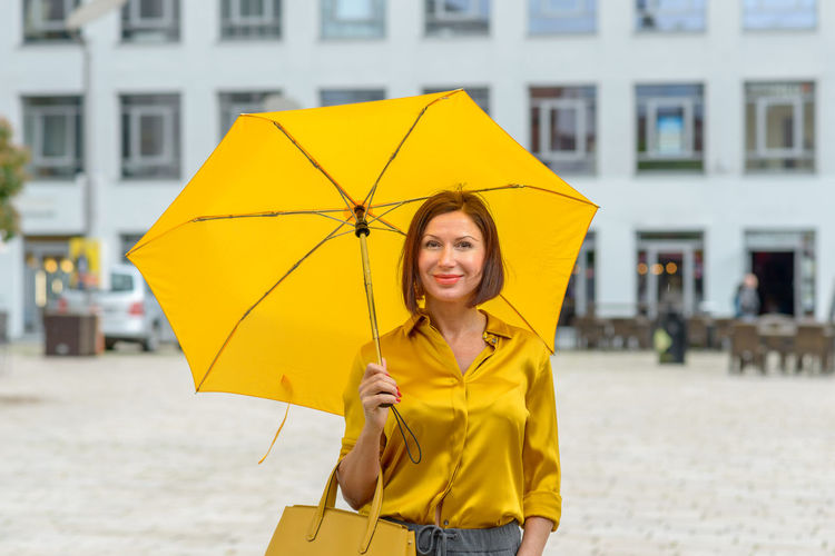 Portrait of woman holding umbrella while standing on road against buildings