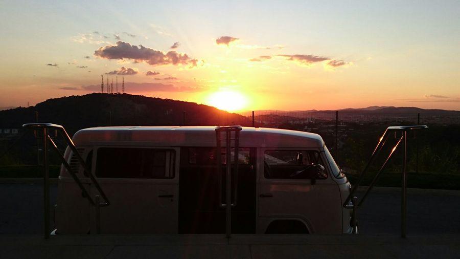 Camper trailer against sky during sunset