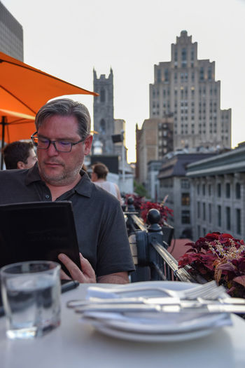 Adult man ordering from menu at rooftop cafe with tall buildings in background Tourism Travel Food And Drink Summer Menu People In The City Urban City Montreal, Canada Montréal Rooftop Bar Rooftop Outside Al Fresco Dining Restaurant Adult Man
