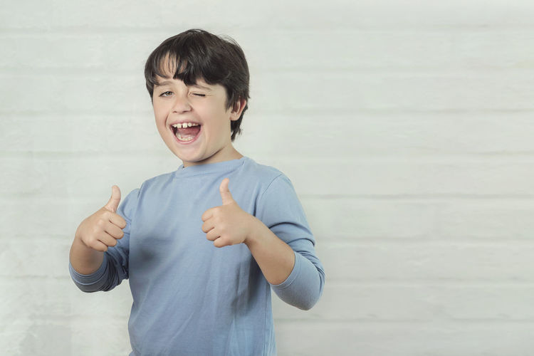 Portrait of boy showing thumbs up signs while standing against wall