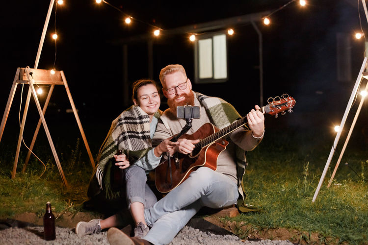 Woman recording with phone by man playing guitar at night