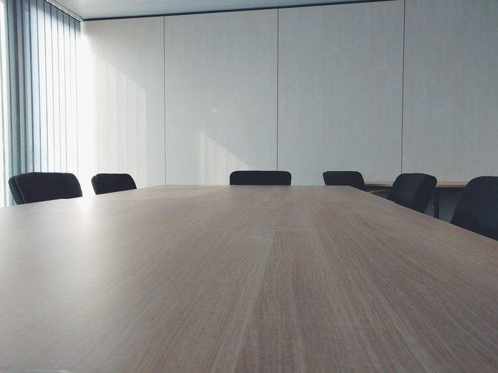 Empty office chairs by table in conference room