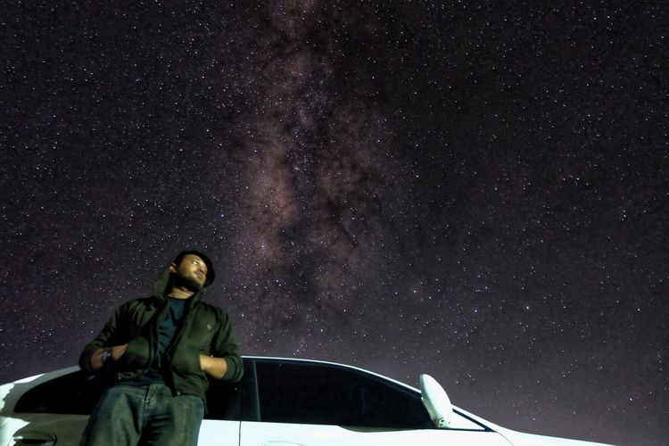 Low angle view of man standing by car against starry sky
