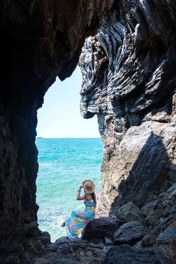 Man sitting on rock by sea