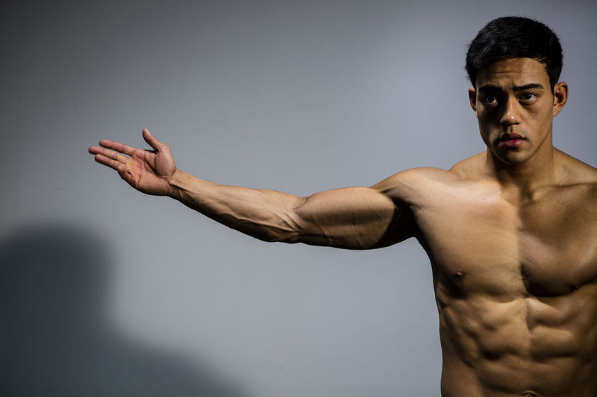 The muscular physique of a male fitness model put on display. The model displays his bicep muscle. Adult Asian  Athletic Body & Fitness Front Facing Human Body Man Nam Vo Vietnamese Arms Spread Bicep Biceps Fit Fitness Model Grey Background Handsome Looking Away From Camera Medium Shot Model Muscles Serious Strong Toned Torso Upper Body