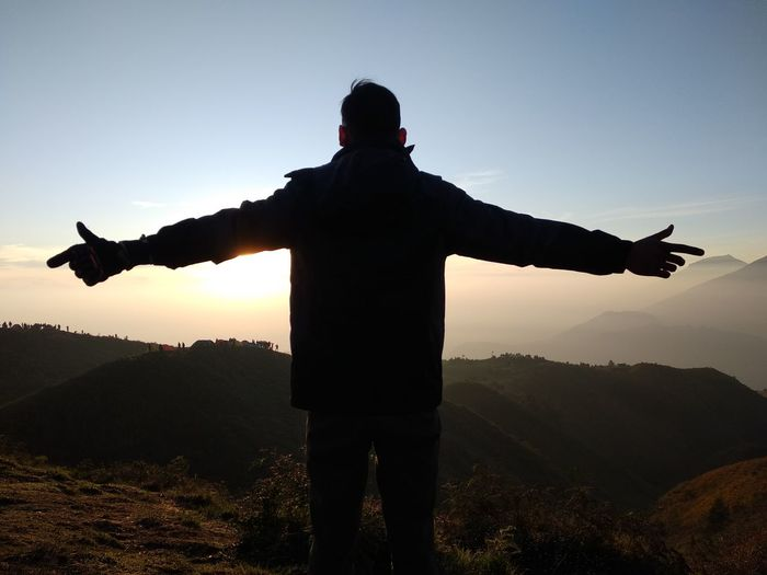 Rear view of man with arms outstretched standing against sky during sunset