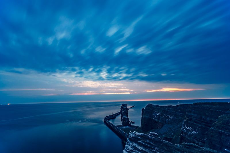 Cliff by sea against cloudy sky