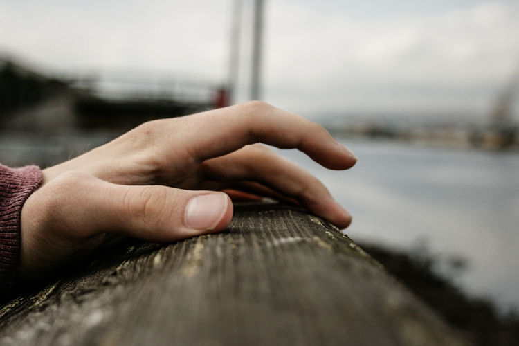 Close-up of hand on railing against sky