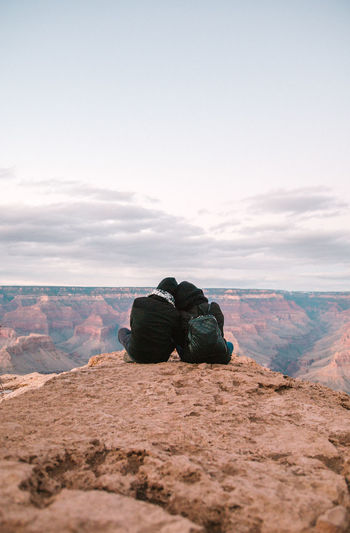 Couple sitting on mountain against sky