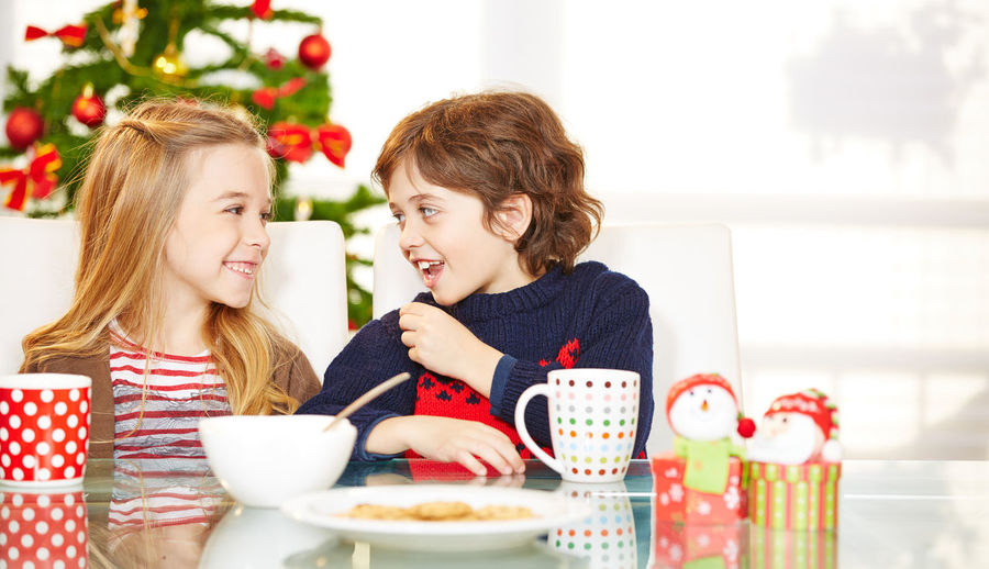 Smiling bother and sister eating food while sitting at dining table at home