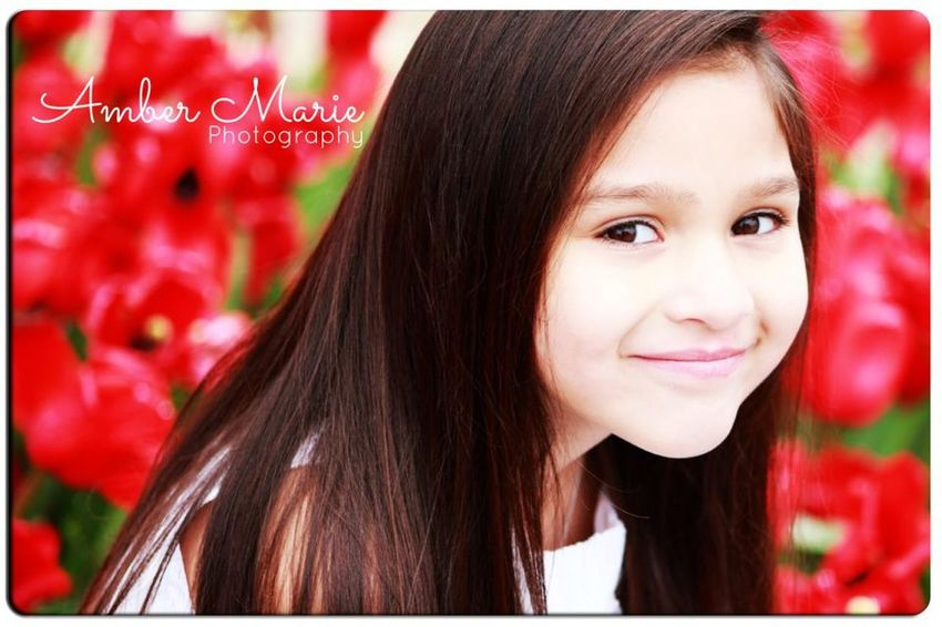 """Just love that facial expression that follows after you tell a child, """"just one more smile, and then we're done."""" #AmberMariePhotography #TheAmberMarie #Beauty #Smile #Red #Background #Spring #Tulips"""