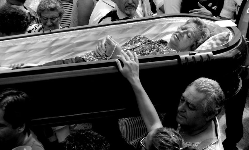 Crowd carrying woman in coffin during fiesta de santa marta de ribarteme