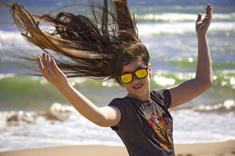 Woman hair blowing in wind at beach with arms raised on sunny day