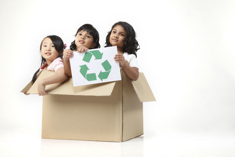 malaysia girl holding recycle sign sitting in cardboard box Cardboard Box Fun Indian Innocence Save The World Save The Nature Box - Container Chinese Elementary Age Emotion Environmental Conservation Future Happiness Leisure Activity Malay Malaysia Playful Portrait Recycle Smiling Studio Shot Symbol Togetherness White Background Women