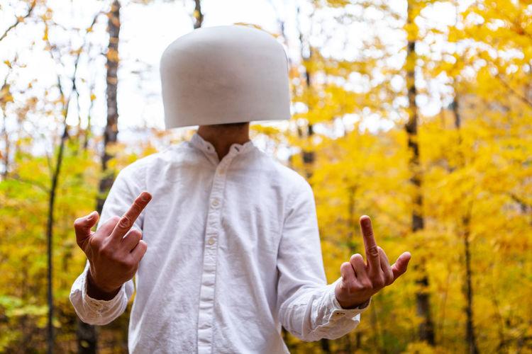 Man wearing bowl on head gesturing against trees