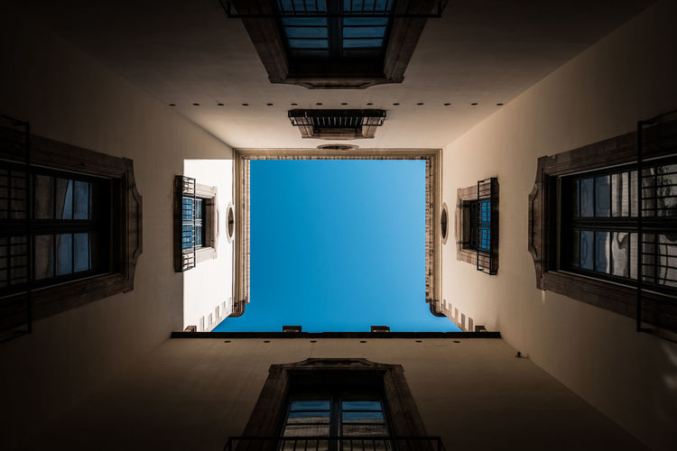 A courtyard hidden in the narrow streets of Barcelona, Spain. Architecture Barcelona Catalunya Old Town SPAIN Streets Summertime Travel Travel Photography Architecture Photography Blue Sky Built Structure Courtyard  Day Fujifilm Historic No People Old Buildings Old House Sky Street Street Photography Streetphotography Sunshine Windows