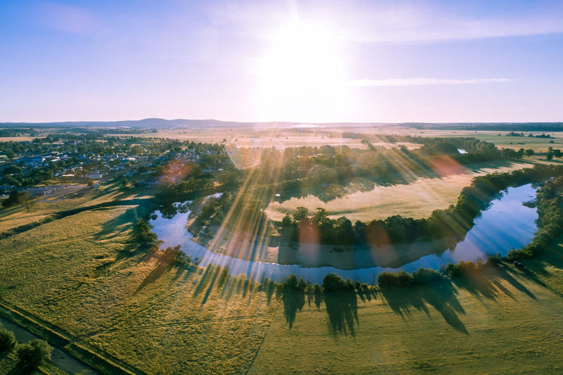 Sunset over snowy river bend with lens flare - aerial view
